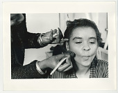 view Young woman having make-up applied to face digital asset: Young woman having make-up applied to face
