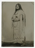 view Standing woman in profile in full Native American dress digital asset: Standing woman in profile in full Native American dress