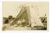 view Two children seated outside striped tent digital asset: Two children seated outside striped tent