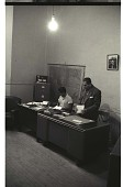 view Officials in Mexico City digital asset: Two officials review documents in an office, Mexico City, Mexico.