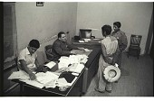 view Braceros Talking to Official digital asset: One official interviews braceros in an office, Mexico City, Mexico, while another official reviews documents.