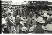 view Bracero Entertainment digital asset: Braceros stand around another bracero who plays the guitar while a woman stands next to him accompanying him with her voice.