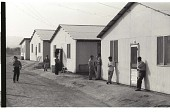 view Braceros at Camp digital asset: Braceros stand outside their living quarters at the Gondo Labor Camp in Watsonville, California.