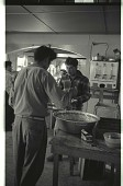 view Braceros at Meal Time digital asset: Braceros put beans on their plates in a dining hall at a Californian camp.
