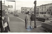 view Braceros in Town digital asset: Braceros stand on a footpath in the town of Watsonville, California.