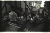 view Braceros Playing Cards digital asset: Braceros sit on beds in a living quarter of a camp and play cards as another writes a letter in the Western United States.