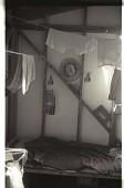view Bracero Living Quarter digital asset: The belongings of a bracero hang over a bed in a living quarter at a Californian camp.