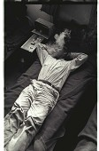 view Bracero Smoking a Cigarette digital asset: A bracero lies in bed and smokes in a living quarter at a Californian camp.