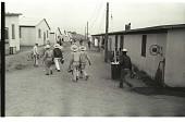 view Braceros at Camp digital asset: Braceros walk between their living quarters in the Gondo Labor Camp, Watsonville.