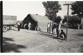 view Braceros at Camp digital asset: Braceros stay in front of a tent at a Californian Camp.