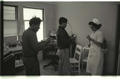 view Bracero at Doctor's Office digital asset: Two braceros stay in the clinical practice of Dr. Stanley Savoy and talk to a nurse in the Salinas Valley, California.