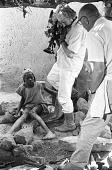 view Cameraman Georges Bracher filming Samuel, son of Dolo, the blacksmith. Ogol du Haut village, Mali digital asset: Cameraman Georges Bracher filming Samuel, son of Dolo, the blacksmith. Ogol du Haut village, Mali