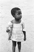 view Child with purple plastic doll, near Kumasi, Ghana digital asset: Child with purple plastic doll, near Kumasi, Ghana