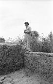 view Eliot Elisofon standing on mud brick wall. Bin village, Mali digital asset: Eliot Elisofon standing on mud brick wall. Bin village, Mali