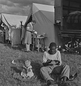view Man shining shoes next to baby playing in Afrikaner Camp, Bronkhorstspruit (South Africa) digital asset: Man shining shoes next to baby playing in Afrikaner Camp, Bronkhorstspruit (South Africa)