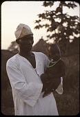 view Hausa barber, Ibrahim Maidonaba, with child, Maikujeri, Nigeria digital asset: Hausa barber, Ibrahim Maidonaba, with child, Maikujeri, Nigeria