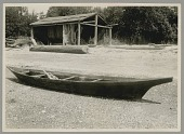 view Fishing Canoe Made by Xabsus, Called Jack Adams, on Beach; Nets Drying Under Open-Walled Structure MAY 1920 digital asset number 1