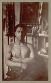 view Portrait (Front) of Johnny Kit Elswa, Interpreter for Judge James G. Swan, with Tattoos on Chest and Forarms; Slate Totem Pole in Background 1885 digital asset number 1