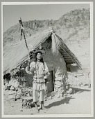 view Pedro Chino, Pascual's Brother, Dressed as Singing Shaman Outside Rancheria's God House digital asset: Pedro Chino, Pascual's Brother, Dressed as Singing Shaman Outside Rancheria's God House