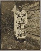 view Chief Cou-Dah-Nah-Ha Wearing Long Shirt with Bear Design And Moccasins Outside Plank House n.d digital asset number 1