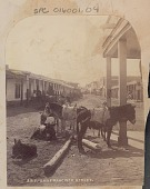 view Street Scene, Showing Saddled Burros, Horse-Drawn Wagon, Group of Non-Native Men and Rows of Masonry Commerical Structures; Royal Baking Powder Sign on Building Post n.d digital asset number 1