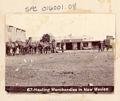 "view Group of Non-Native Men Hauling Goods in Horse-Drawn Wagons, Outside Masonry Buildings Including Restaurant and Shop ? with Sign Reading, ""S Nathan"" n.d digital asset number 1"