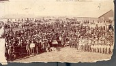view Dakota Indians with Whites At Census Taking; Chief Gall in Center at Tables with Non-Native Men; Wood Frame and Log Buildings in Background n.d digital asset number 1