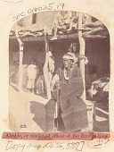 view Man, Governor, Wearing Blanket and with Cane of Office, Outside Adobe Structure; Group in Native Dress Nearby n.d digital asset number 1