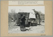 view Lawrence Steel's Wife in Native Dress, Carrying Wood in Basket Attached to Tumpline, Outside Blanket-Covered Wickiup 14 JUN 1906 digital asset number 1
