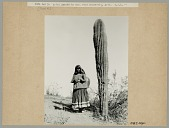 view Woman in Native Dress, Carrying Pitch-Covered Basket Jug Attached to Tumpline, Next to Large Cactus n.d digital asset number 1