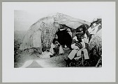 view Shaman Wearing Blanket; Woman with Dog Outside Wickiup digital asset: Shaman Wearing Blanket; Woman with Dog Outside Wickiup