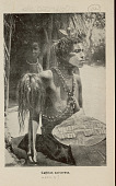 view Sorceress in Costume with Body Paint and Holding Animal Skin Shield and Scalp? Pole; with Young Boy Outside Thatch House n.d digital asset number 1