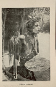 view Sorceress in Costume with Body Paint and Holding Animal Skin Shi Eld and Scalp? Pole; with Young Boy Outside Thatched House n.d digital asset number 1