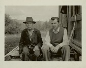 view Julian Steward with man (possibly Steward's informant, Chief Louis Billy Prince) seated outside of wood building with bow and quiver of arrows leaning against wall nearby, 1940 digital asset number 1