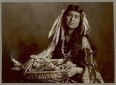 view Woman with blanket, wearing corn husks in her hair and holding basket containing corn and apples Copyright 10 FEB 1906 digital asset number 1