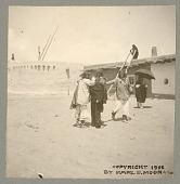 view Three men and woman with umbrella in plaza outside adobe house and Squash Kiva Copyright 11 APR 1906 digital asset number 1