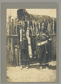 view Two men in Plains-style clothing outside log fence and brush structure Copyright 04 NOV 1907 digital asset number 1