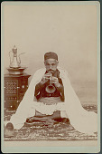 view Portrait of Man in Costume, Blowing Horn, Shoes and Pouch On Rug; Brass Ewer and Basin on Carved Wooden Inlaid Table Nearby n.d digital asset number 1
