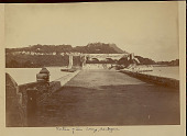 view View of Stone Fortress and Roadway Built Over Water with Two Boys Fishing from Stone Wall; Buildings Atop Mountain and Village of Pole and Thatch Houses on Opposite Bank Across Water 1870 digital asset number 1