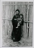view Amahuaca Woman Wearing Face Paint and Bead Necklaces and Holding Young Girl; Both in Costume Outside Bamboo House JUL 1910 digital asset number 1