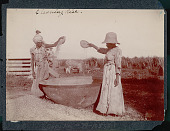 view Two Women in Costume and Winnowing Rice Into Large Container; Men and Oxen? Near Water Wheel? Behind Them digital asset: Two Women in Costume and Winnowing Rice Into Large Container; Men and Oxen? Near Water Wheel? Behind Them