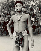 view Man, Warrior, with Mithun (Wild Cow) Horns, Chest Tattoo And Effigy Head Necklace, Indicating Successful Headhunting, And Wearing Ear Plugs and Cowrie Shell Belt 1954 digital asset number 1
