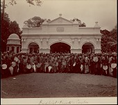 view Group of Buddhist men and boys, some with fans and umbrellas, outside stone entranceway, undated digital asset number 1