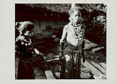 view Two Girls in Costume and with Ornaments Outside Pole and Mud House with Holes (for Ventilation?) and Thatch Roof; Clay Jars Nearby 1965 digital asset number 1