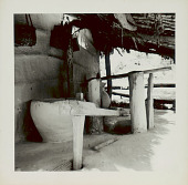 view Wood Trip-Hammer Pestle Used for Rice-Hulling on Porch of Pole and Mud House with Thatch Roof; Large Clay? Container For Storing Rice; Baskets Hanging on Wall 1965 digital asset number 1