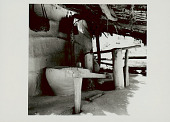 view Wood Trip-Hammer Pestle Used for Rice-Hulling on Porch of Pole and Mud House with Thatch Roof; Large Clay? Container For Storing Rice Nearby; Baskets Hanging on Wall 1965 digital asset number 1