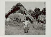 view Woman in Costume and with Ornaments, Carrying Basket on Head And Infant on Back Outside Pole and Mud House with Thatch Roof And Squash Growing on Top and Thatch Awning 1965 digital asset number 1