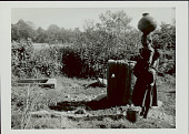 view Woman in Costume and with Ornaments, Carrying Infant on Back And Clay Water Jar on Head at Well?; Metal Bucket and Wood Trough? Nearby 1965 digital asset number 1