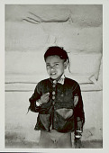 view Young Boy in Costume and with Ornaments Ouside Pole and Mud House with Animal Motifs in Mud Bas-Relief on Wall 1965 digital asset number 1