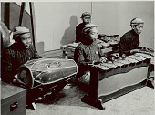 view Four Men in Costume, Playing Mukur-Tarang (Percussion Instrument ), Dhol (Barrel-Shaped Drum), and Unidentified Percussion Instrument 1956 digital asset number 1